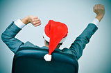 man with a santa hat stretching his arms in his office chair