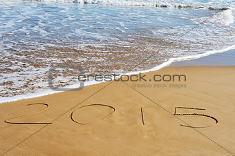 2015, as the new year, written on the sand of a beach