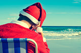 santa claus taking a nap on the beach
