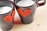cups of milk with decorative hearts on wood table, concept of valentine day