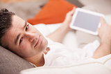 relaxed man using a tablet at home