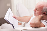 man reading a newspaper on a sofa