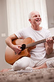 mature man playing guitar at home