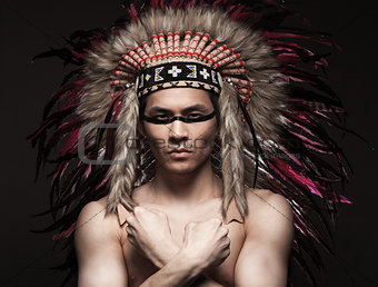 Portrait of the indian strong man posing with traditional native american make up