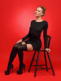 woman in a black dress and stockings sitting on the chair