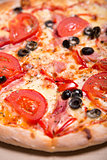 Close-up shot of delicious Italian pizza with ham, tomatoes and