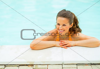 Portrait of happy young woman in pool looking on copy space