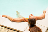 Relaxed young woman laying in pool. rear view
