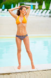 Full length portrait of relaxed young woman standing at poolside