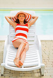 Relaxed young woman laying on sunbed