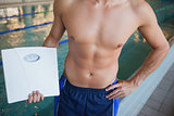 Mid section of a shirtless fit swimmer with weighing scales by pool