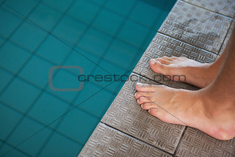 Close up low section of barefeet by pool