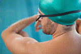 Close up rear view of a fit swimmer by the pool