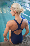 Rear view of a fit female swimmer sitting by pool