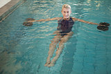 Female swimmer working out with foam dumbbells in swimming pool