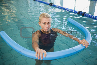 Fit female swimming with foam roller in pool