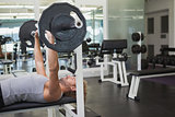 Young muscular man lifting barbell in gym