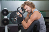 Side view of muscular man lifting barbell in gym