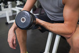 Mid section of man exercising with dumbbell in gym
