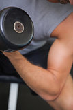 Close up mid section of man exercising with dumbbell