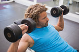 Side view of man exercising with dumbbells in gym