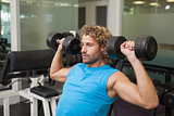 Young man exercising with dumbbells in gym