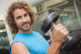 Handsome man exercising with dumbbell in gym