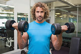 Handsome young man exercising with dumbbells in gym