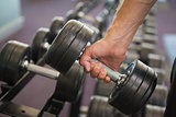 Close up of hand holding dumbbell in gym