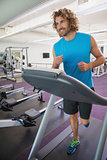Smiling man running on treadmill in gym