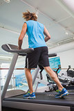 Rear view of man running on treadmill in gym