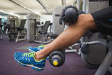 Low section of man doing leg workout at gym