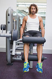 Portrait of handsome man doing leg workout at gym