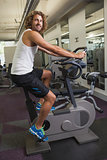 Side view of man working out on exercise bike at gym
