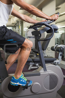 Cropped man working out on exercise bike at gym