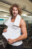 Smiling handsome trainer with clipboard in gym
