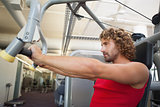 Side view of man working on fitness machine at gym