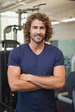 Smiling handsome trainer with arms crossed in gym