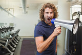 Portrait of trainer shouting into bullhorn in gym