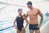 Fit couple swimmers by pool at leisure center