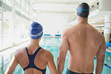 Rear view of couple swimmers by pool at leisure center