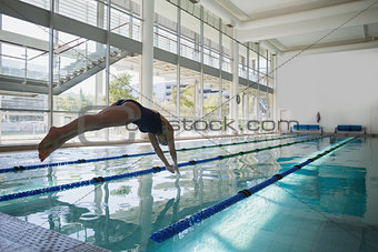 Fit swimmer diving into the pool at leisure center