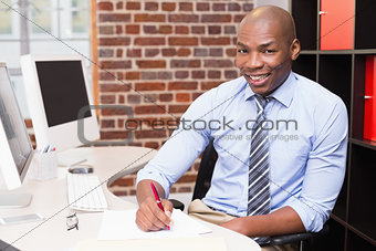 Portrait of businessman writing document at desk