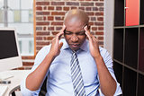 Businessman with severe headache in office
