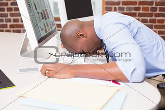 Businessman resting head on computer keyboard in office