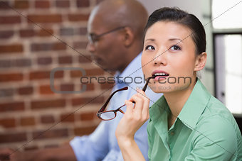 Thoughtful young businesswoman in office