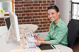 Smiling female photo editor using computer in office
