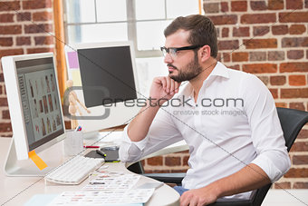 Concentrated male photo editor using computer in office