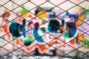 abstract graffiti through metal bars fence