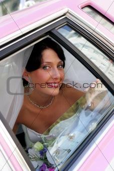 Smiling bride in wedding car limousine